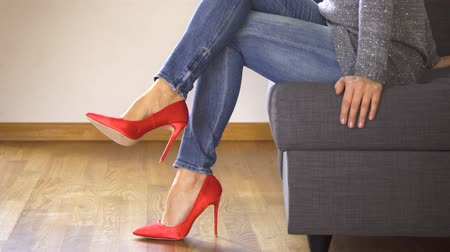 işlemek : Woman on couch in red high heels shows and crosses sexy and slim long legs