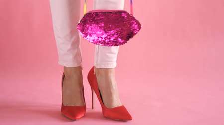 female legs on coral background with purse during feminine and elegant walk