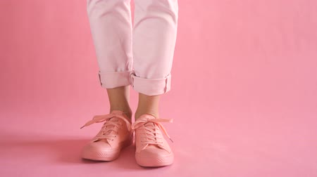 Close up of shapely young female legs walking in sneakers on coral background Стоковые видеозаписи