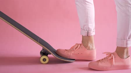 Close up of girl legs with skateboard starts riding on coral background Стоковые видеозаписи