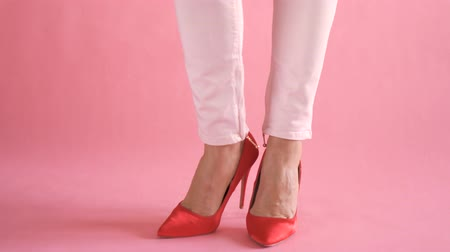Slim female legs on coral background in pants during feminine and elegant walk
