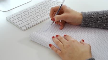 follower : Female hands write note in notebook next to white computer keyboard Stock Footage