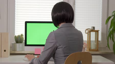 ayrıntılı : back view of woman working on computer keyboard in front of display with isolated green screen