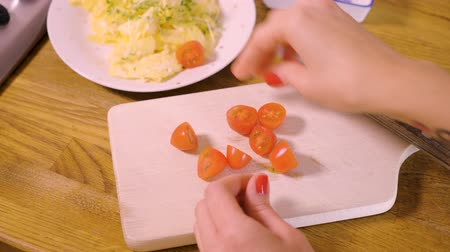 scrambled eggs : woman is cutting small tomatoes and putting them together with scrambled eggs on white plate in home kitchen
