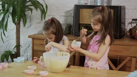 przedszkolak : two little girls put cream on the molds to make cupcakes