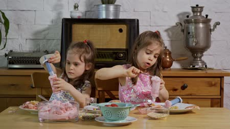 tatlı çörek : two little girls put on a cream and decorate delicious cupcakes on a wooden table