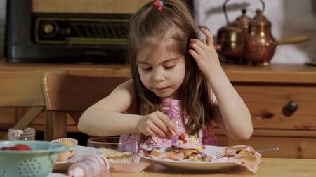 przedszkolak : little girl decorates and eats delicious cupcakes