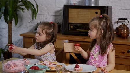 vdolky : two little girls put on a cream and decorate delicious cupcakes on a wooden table