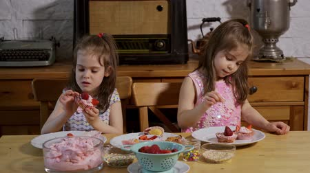 przedszkolak : two little girls put on a cream and decorate delicious cupcakes on a wooden table
