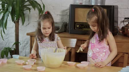 tatlı çörek : two little girls put cream on the molds to make cupcakes
