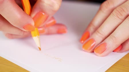 notas : woman is holding an orange pencil and makes notes on a white paper Stock Footage