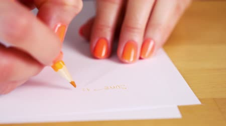 držení : woman is holding an orange pencil and makes notes on a white paper Dostupné videozáznamy