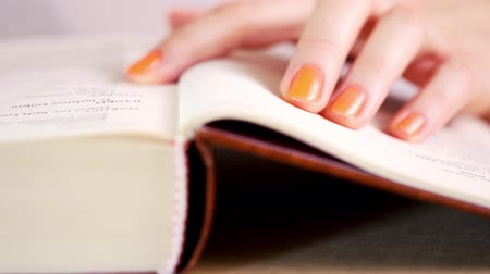 biblia : view of a womans hand reading an old book and writing notes