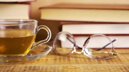 alfabetização : old books and hot black tea in a glass mug on a shelf Stock Footage