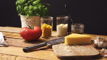 pronto a comer : Shredded cheese with fresh basil and juicy tomato on  wooden kitchen table Stock Footage