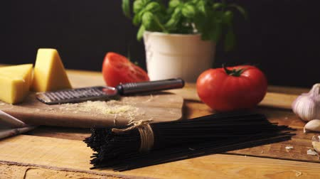 cheese types : Shredded cheese with fresh basil and italian spaghetti on wooden kitchen table