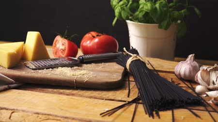 pronto a comer : Shredded cheese with fresh basil and italian spaghetti on wooden kitchen table