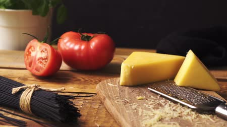 пармезан : Shredded cheese with fresh basil and italian spaghetti on wooden kitchen table