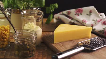 capers : Cheese on chopping board and grater with fresh basil on wooden kitchen table