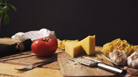 wooden type : Shredded cheese with fresh basil and italian spaghetti on wooden kitchen table