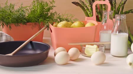 укроп : Spring young vegetables with eggs and with milk and  frying pan on  wooden table