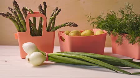chives : Spring young vegetables in coral containers on wooden table