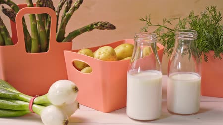 chives : Spring young vegetables in coral containers and bottles with milk on table
