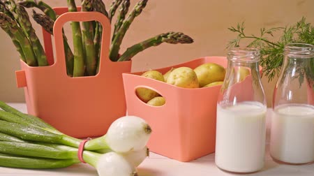 cebolinha : Spring young vegetables in coral containers and bottles with milk on table
