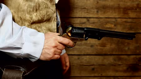 batı : Gunslinger pulls out the gun on wooden background Stok Video