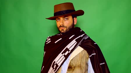 olhares : Footage of a gunslinger looking at camera while smoking a cigar. Shooting on green screen.