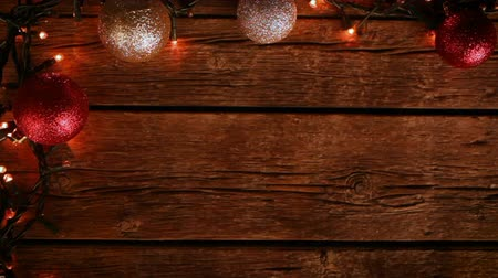 Christmas decoration corner with balls and lights on wooden table.