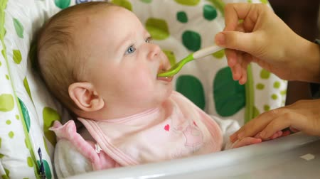 Baby eats first meals with fruit. Mom makes eating the pear homogenized with a spoon.