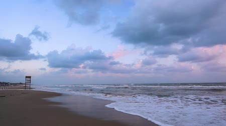 Panoramic view of the beach with shaky sea at sunset.