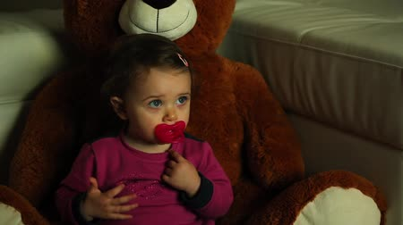 Portrait of little baby girl watches TV in the dark with her plush bear. Vídeos