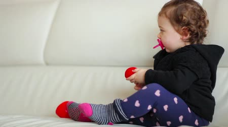 Toddler baby girl playing and dancing on the sofa