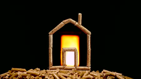 combustão : Miniatures house made with wood pellets. Heating concept with combustion chamber in the background.