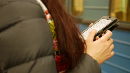 young woman reading an electronic book in subway