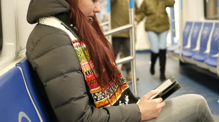Young woman read e-book in subway train at metro 影像素材