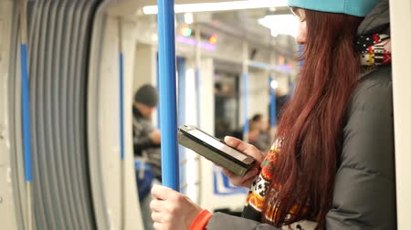 Young woman read e-book in subway train at metro Стоковые видеозаписи