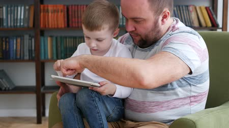 Daddy and son websurfing on digital tablet at home Стоковые видеозаписи