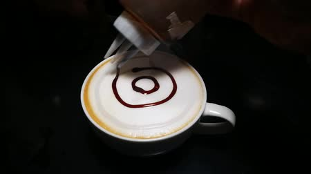 pitcher : Step homemade latte art coffee with chocolate sauce and caramel sauce  on Milk foam in kitchen. Lined pattern Flower  on latte art coffee.   Even if its not a barista, you can do it. Stock Footage