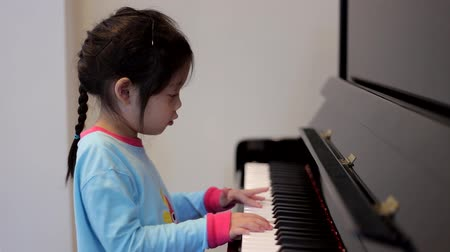 lesson : Little Girl is Playing Piano at Her Home With Happiness.