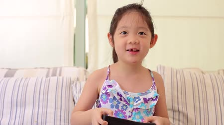 eğlence oyunları : Little Kid, a Girl, Enjoys Playing Video Game at Home