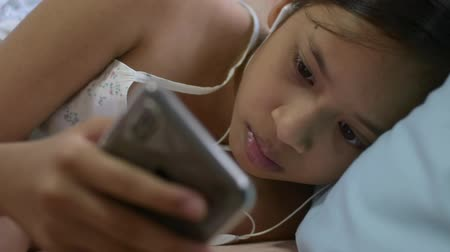 connectivity : Cute girl in casual dress using mobile phone with headphones lying on the bed. Stock Footage