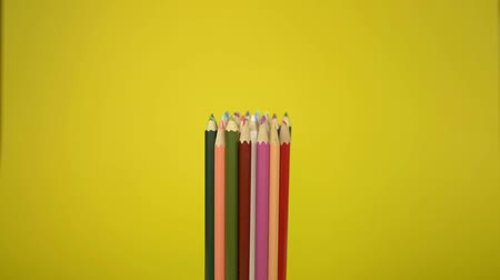 kötött : Colored pencils that are tied together are fall disorderly on yellow background, Unity and cooperation of organization concept.