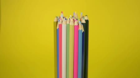 bekötött : Colored pencils that are tied together are fall disorderly on yellow background, Unity and cooperation of organization concept.