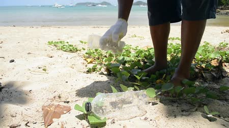 environmental awareness : Cleaner collecting garbage on the sandy beach into green plastic bag, Plastic bottles are collected on the beach, Volunteer cleaning the beach, Environmental awareness concept. Stock Footage
