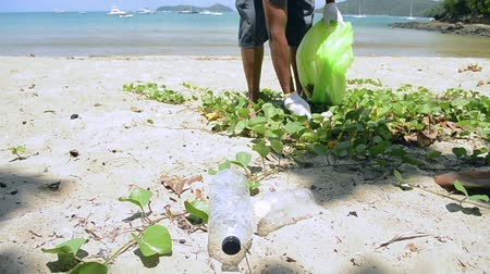poluir : Cleaner collecting garbage on the sandy beach into green plastic bag, Plastic bottles are collected on the beach, Volunteer cleaning the beach, Environmental awareness concept. Stock Footage