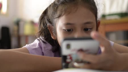 phone entertainment : Little cute asian girl using and watching video from mobile phone on study desk at home.