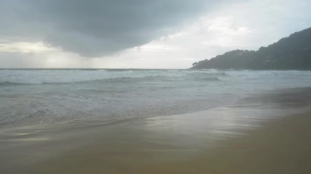 monção : Scenery of tropical sandy beach with foam formed by waves breaking on a seashore and rain clouds in the sky at karon beach, Phuket, Thailand. Vídeos